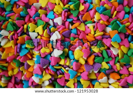 Closeup shot of a very small colorful candies in heart shape used for cakes decorations. - stock photo