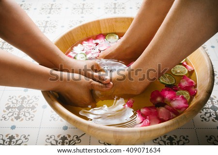 Closeup shot of a woman feet dipped in water with petals in a wooden bowl. Beautiful female feet at spa salon on pedicure procedure. Shallow depth of field with focus on feet.  - stock photo