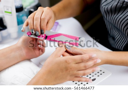 Closeup shot of a woman in a nail salon receiving a manicure by a beautician