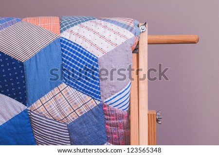 Closeup shot of antique quilt displayed on wooden rack.