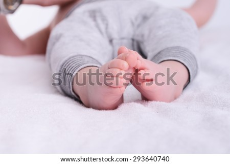 closeup shot of baby foot laying down on a white blanket