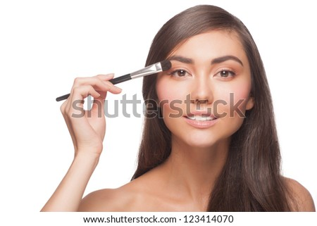 Closeup shot of beautiful woman applying eyeshadow on eyelid using makeup brush - stock photo