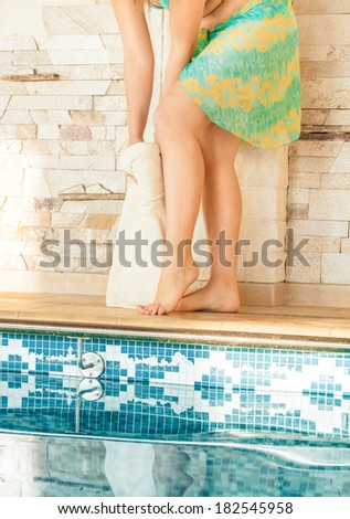 Closeup shot of beautiful woman drying legs with towel at swimming pool - stock photo