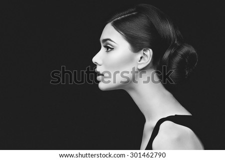 Closeup shot of beautiful young woman profile over black background - stock photo