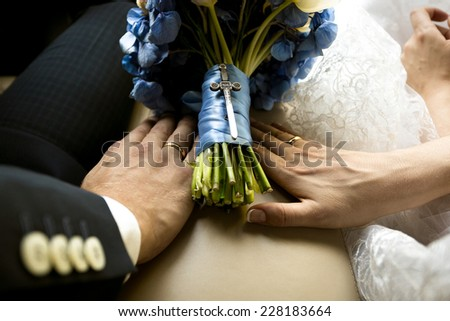 Closeup shot of bride and groom holding hands on wedding bouquet at car - stock photo