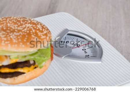 Closeup shot of burger on weighing scale - stock photo