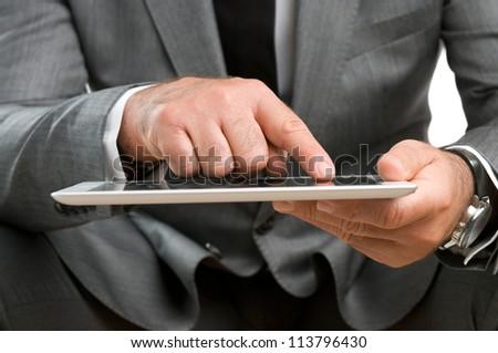 Closeup shot of businessman working on digital tablet - stock photo