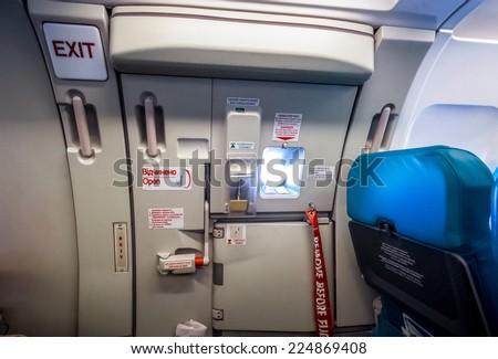 Closeup shot of emergency exit door in airplane - stock photo