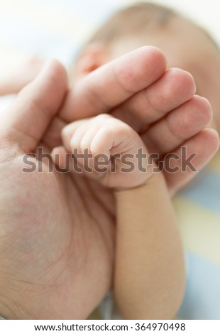 Closeup shot of father holding newborn baby hand. Image with soft focus
