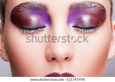 Closeup shot of female closed eye with evening violet eyes shadows, white eyelashes and purple lips makeup