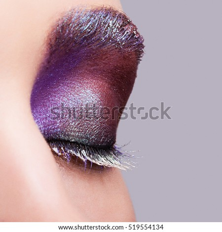 Closeup shot of female closed eye with evening violet purple eyes shadows and white eyelashes makeup