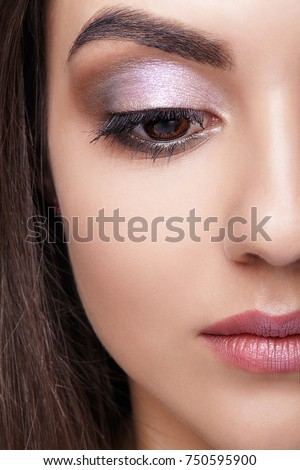 Closeup shot of female face with day makeup eyes shadows. Looking down