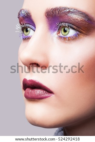 Closeup shot of female green pistachio colour eye with evening violet eyes shadows, white eyelashes and purple lips makeup