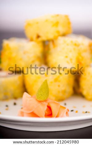 Closeup shot of fresh ginger sliced with wasabi sauce on top with sushi rolls in the background selective focus - stock photo