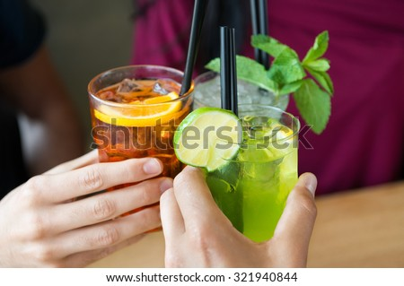 Closeup shot of friends toasting with cocktails. Young people drinking at aperitif. Shallow depth of field with focus on friends hand toasting juice glass. Close up of hands holding a cocktail glass. - stock photo