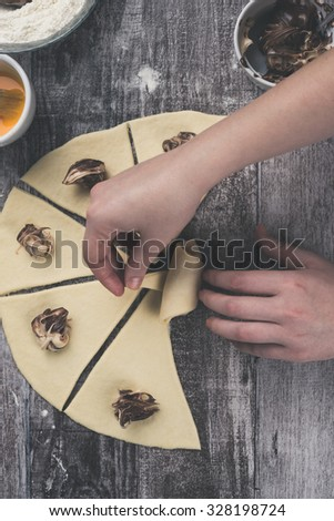 Closeup shot of gently young woman hands making a beautiful and delicious homemade rolls with nougat creme. Photographed from above. Processed to mach old film look. - stock photo