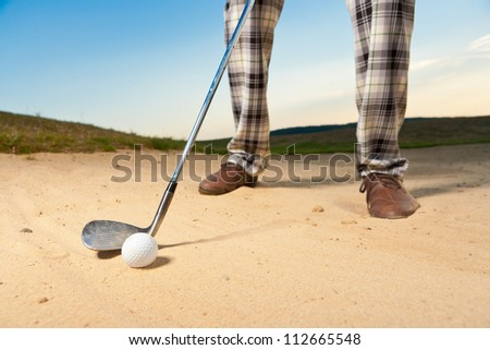 closeup shot of golf ball with golf club right before tee off from bunker - stock photo