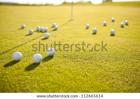 closeup shot of golf balls on green golf course - stock photo