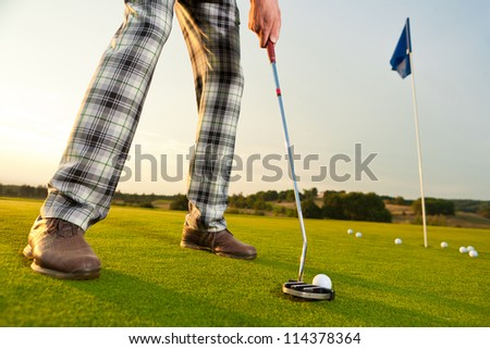closeup shot of golfer  with golf club during putting the ball in hole training-1 - stock photo