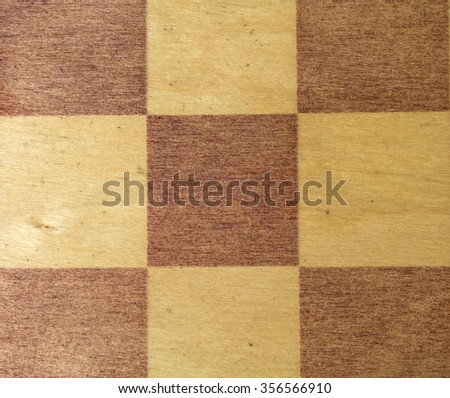 Closeup shot of light and dark brown checks on vintage wooden chessboard. - stock photo