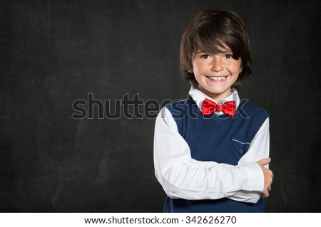 Closeup shot of little boy standing with armcrossed isolated on blackboard. Smiling cute male child with red papillon looking at camera. Lovable boy wearing waistcoat and red bow tie with copy space.  - stock photo