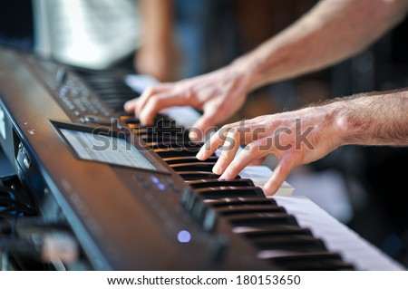 closeup shot of male hands playing the piano .Human hands playing the piano on the party . Man playing the synthesizer keyboard  - stock photo
