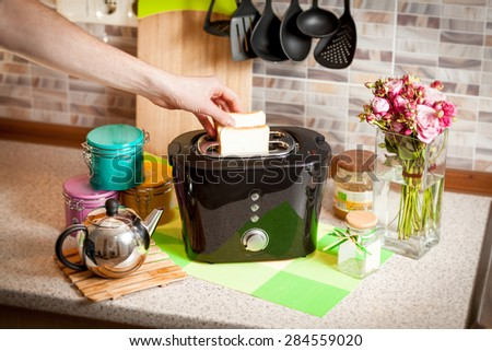 Closeup shot of man putting bread in toaster at kitchen - stock photo