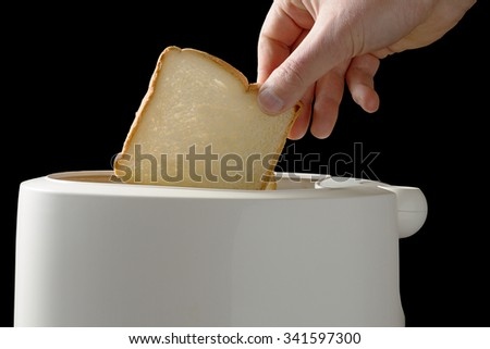 Closeup shot of man putting white bead slices in toaster isolated on black background with clipping path. - stock photo