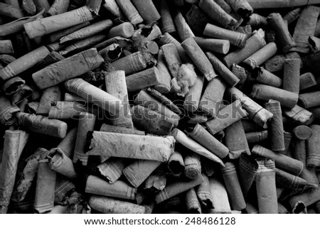 closeup shot of many burnt cigarette butts black and white - stock photo