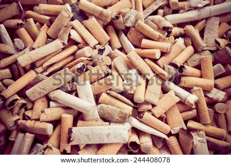 closeup shot of many burnt cigarette butts color toned - stock photo