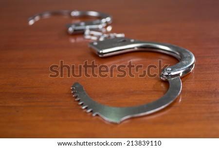 Closeup shot of metallic open handcuffs on wooden table - stock photo