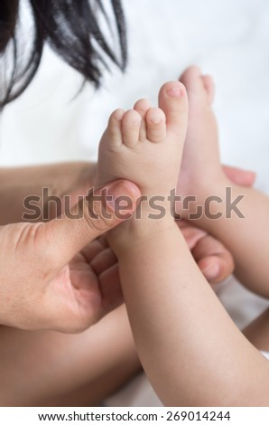 closeup shot of mother's hands holding softly baby's feet - stock photo