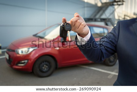 Closeup shot of sales manager holding car keys against new car - stock photo