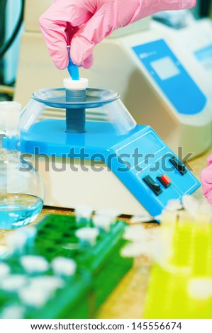 closeup shot of scientist's hand in pink protective glove putting from test tube into centrifuge