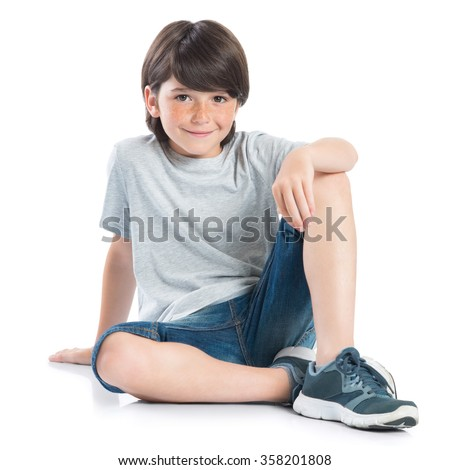 Closeup shot of smiling little boy sitting on white background. Adorable child in casual looking at camera. Happy cute boy sitting on floor and looking at camera. - stock photo