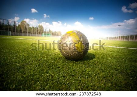 Closeup shot of soccer football on grass field at sun beams - stock photo