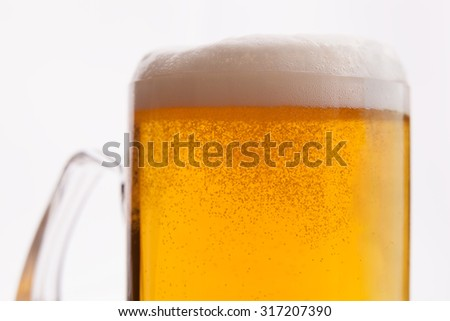 Closeup shot of sparkling light beer on isolated background - stock photo