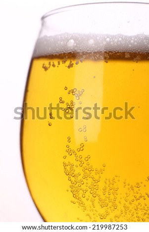 Closeup shot of sparkling light beer over a hi key background