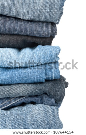 Closeup shot of stack of jeans isolated on white background - stock photo