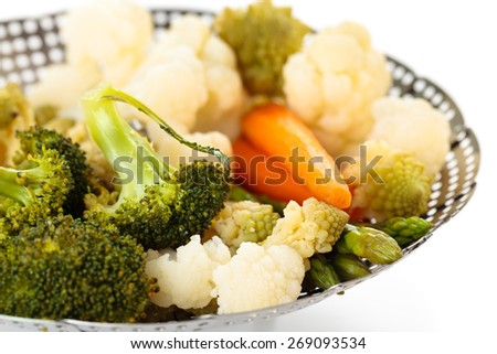 Closeup shot of steamed vegetables on steamer. Isolated on white background. - stock photo