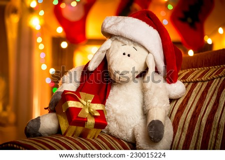 Closeup shot of toy sheep with gift box at decorated for Christmas living room - stock photo
