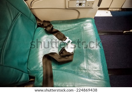 Closeup shot of unfastened belt on seat at airplane - stock photo