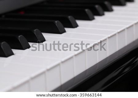 closeup shot of white keys and black keys on keyboard of a piano - stock photo