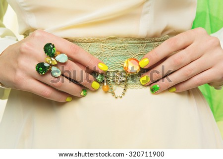 Closeup shot of woman hands with ring and yellow, green manicure holding brooch on belt