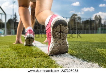 Closeup shot of woman in sneakers standing on white line drawn on grass