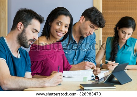 Closeup shot of young african woman looking at camera while her friends studying. Team of students preparing the university exam. Young men and women writing note in notebook.