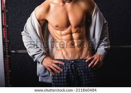 Closeup shot of young bodybuilder with abs. Fit muscular Caucasian man showing his abdominal muscles. Handsome man's torso against dark background. - stock photo