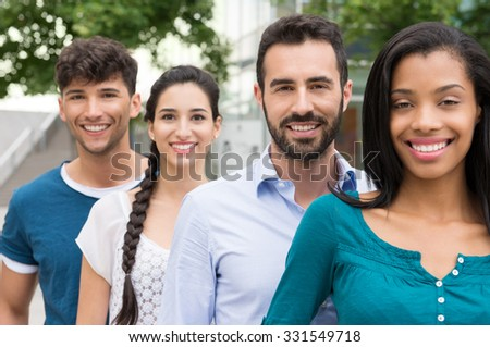 Closeup shot of young friends standing in a row outdoor. Happy group of men and women smiling and looking at camera. Happy young friends outside.