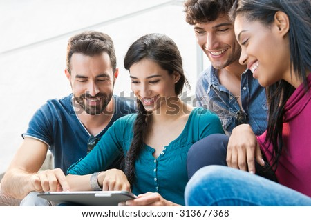 Closeup shot of young men and women looking at digital tablet. Happy smiling group of friends sitting outdoor using digital tablet.   Happy young woman pointing on a digital tablet. - stock photo