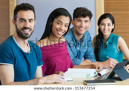 Closeup shot of young men and women studying. Portrait of happy student smiling and looking at camera. A team of students sitting in a row behind the table. - stock photo